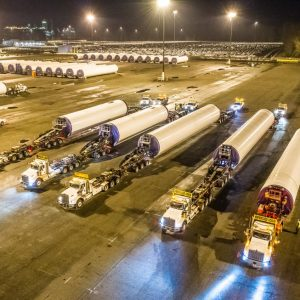 Omega Morgan specialized transportation semi trucks lined up with wind turbine segments in tow