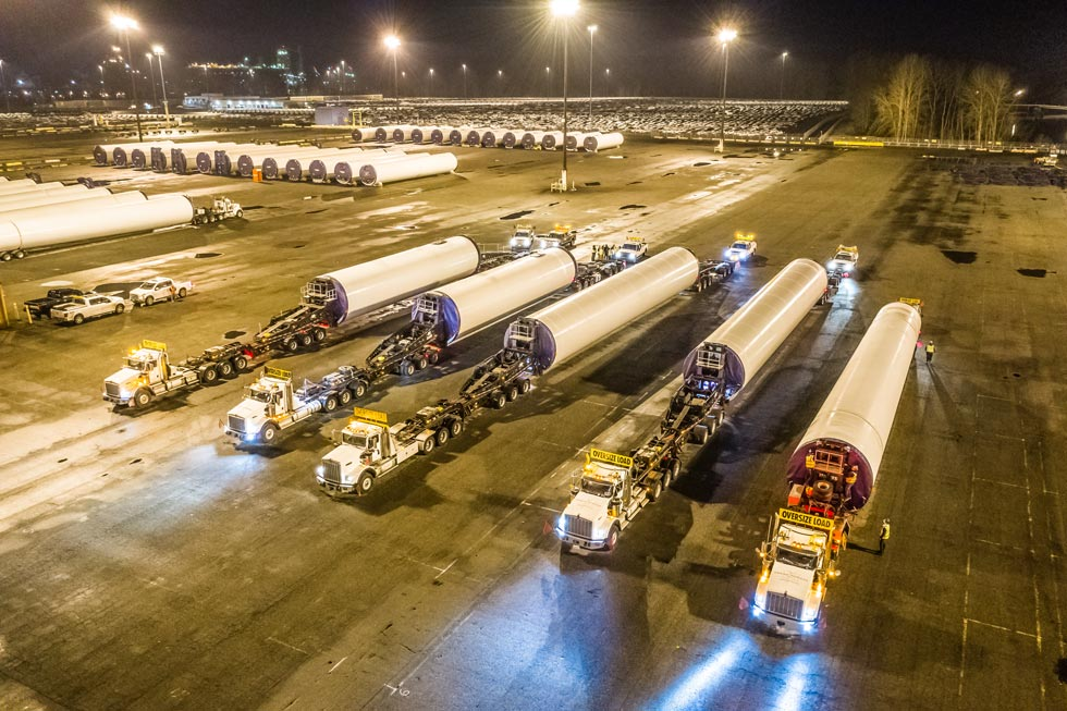 five Omega Morgan trucks with wind turbine parts at night ready to move the superloads
