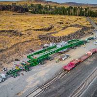 selected thumbnail button of aerial perspective of the huge transformer, trailer, trucks and crew for this specialized moving project with a total transport weight of nearly one million pounds and the length of a football field near the Washington Oregon border