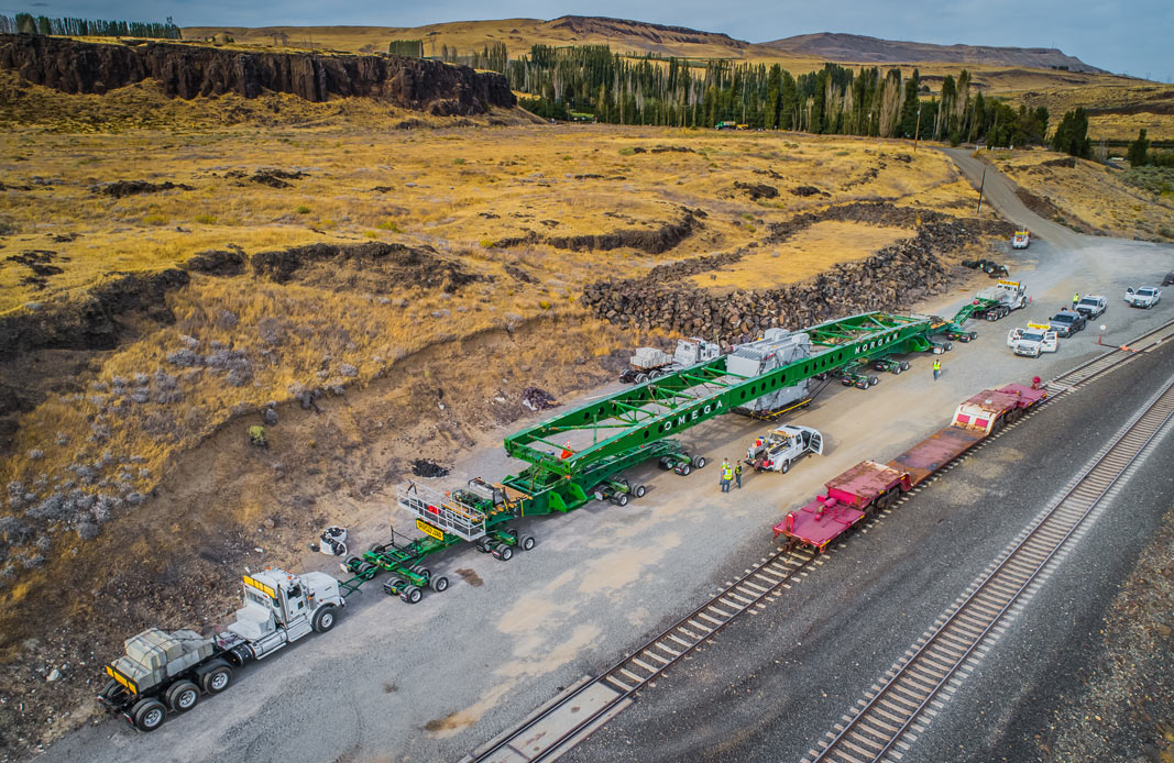 aerial perspective of the huge transformer, trailer, trucks and crew for this specialized moving project with a total transport weight of nearly one million pounds and the length of a football field near the Washington Oregon border