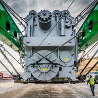 selected thumbnail button of man walks past huge transformer strapped into green Omega Morgan trailer the length of a football field in Klickitat County, Washington