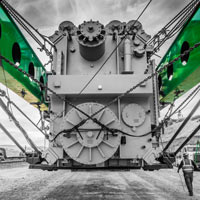 deselected thumbnail button of man walks past huge transformer strapped into green Omega Morgan trailer the length of a football field in Klickitat County, Washington