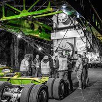 deselected thumbnail button of Omega Morgan crewmembers stand near an enormous transformer for an onsite safety meeting prior to the superload transport
