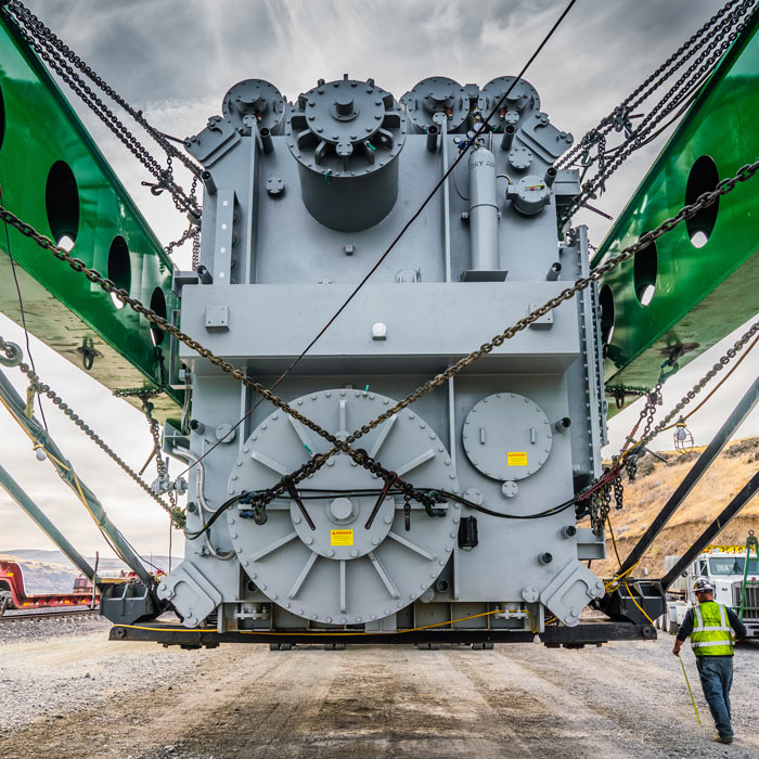 man walks past huge transformer strapped into green Omega Morgan trailer the length of a football field