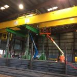 Omega Morgan's machinery moving crews lift an overhead crane with a gantry system at a Mcminville, Oregon facility