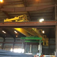 selected thumbnail button of inside a steel mill, a double girder bridge crane is swapping positions with another crane by being lifted by a green omega morgan gantry system