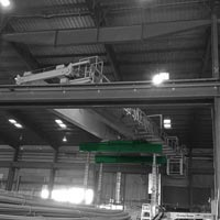 deselected thumbnail button of inside a steel mill, a double girder bridge crane is swapping positions with another crane by being lifted by a green omega morgan gantry system