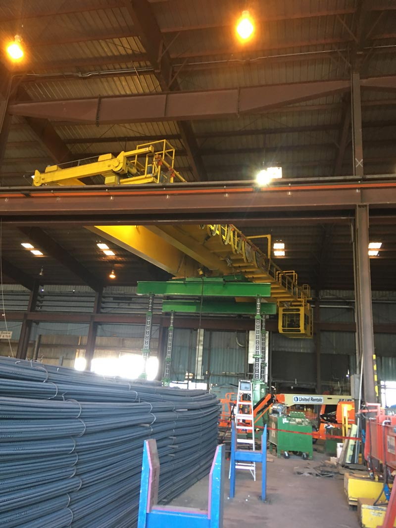 inside a steel mill, a double girder bridge crane is swapping positions with another crane by being lifted by a green omega morgan gantry system