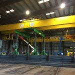 two large yellow double girder bridge cranes are being lifted by a green Omega Morgan gantry system inside a steel mill in McMinville, Oregon