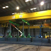 selected thumbnail button of two large yellow double girder bridge cranes are being lifted by a green Omega Morgan gantry system inside a steel mill in McMinville, Oregon