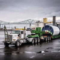 selected thumbnail button of Omega Morgan specialized transportation tractor pulling a schnabel trailer holding a Vestas wind turbine tower section in front of the Longview bridge in Longview, Washington