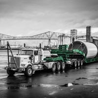 deselected thumbnail button of Omega Morgan specialized transportation tractor pulling a schnabel trailer holding a Vestas wind turbine tower section in front of the Longview bridge in Longview, Washington