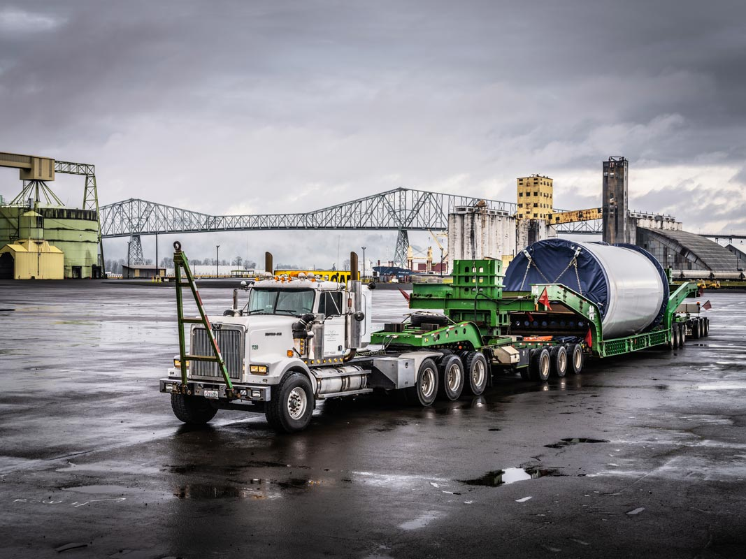 Omega Morgan specialized transportation tractor pulling a schnabel trailer holding a Vestas wind turbine tower section in front of the Longview bridge in Longview, Washington