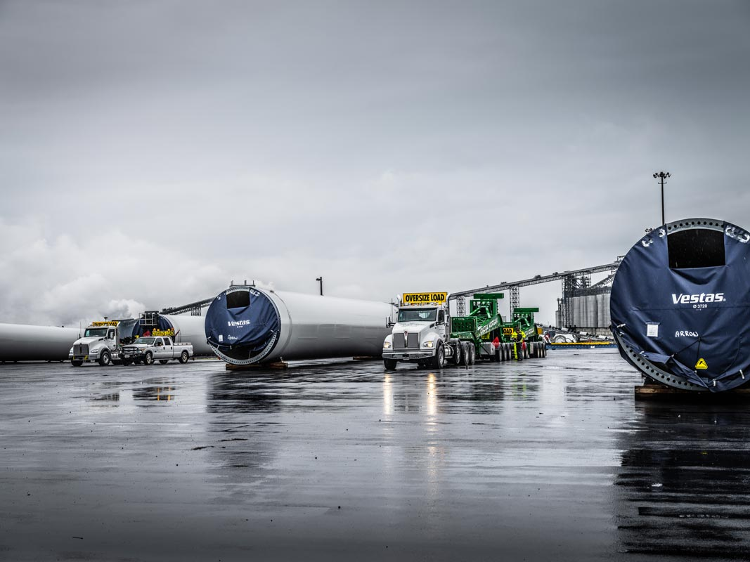 Vestas wind turbine tower sections at the Port of Longview staged to load onto Omega Morgan branded schnabel trailers
