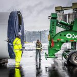 two Omega Morgan specialized transportation crew members between a vestas wind turbine tower section and a schnabel trailer that is ready to be loaded at the Port of Longview