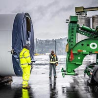 selected thumbnail button of two Omega Morgan specialized transportation crew members between a vestas wind turbine tower section and a schnabel trailer that is ready to be loaded at the Port of Longview