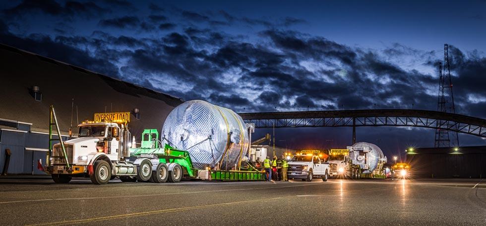 Omega Morgan specialized transportation tank trailer transporting an adsorber vessel at night