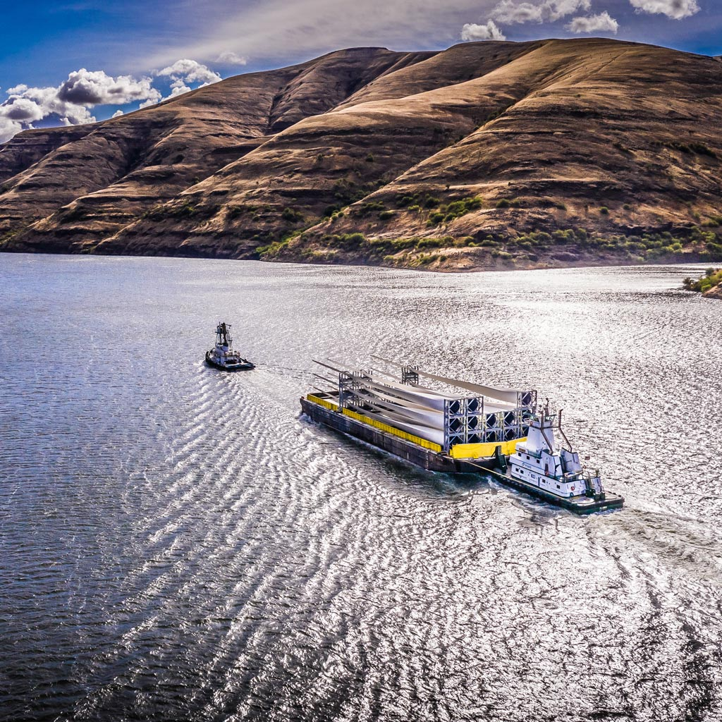 A barge transporting wind turbine blades to the Port of Lewiston as part of a groundbreaking transportation solution created and executed by the Omega Morgan team