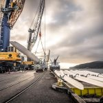 Wind turbine blades being loaded onto a barge by the Omega Morgan team at the Port of Longview