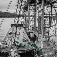black and white and green thumbnail of omega morgan millwright crews working on a grain spout at Kalama Export