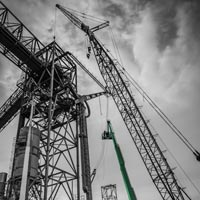 black and white and green thumbnail of two 150 foot manlifts and crane near grain spout for repairs