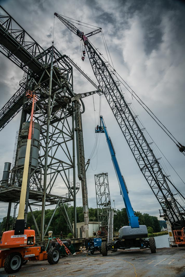 two 150 foot manlifts and crane near grain spout for repairs