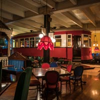 full color thumbnail of antique trolley car parked inside Old Spaghetti Factory