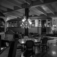 black and white thumbnail of antique trolley car parked inside Old Spaghetti Factory