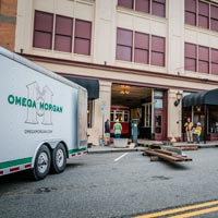 full color thumbnail of omega morgan trailer and outside of Old Spaghetti Factory while antique trolley is being put into the building
