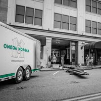 black and white and green thumbnail of omega morgan trailer and outside of Old Spaghetti Factory while antique trolley is being put into the building