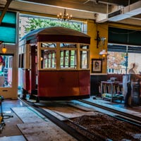 full color thumbnail of antique trolley being transported into the Old Spaghetti Factory on slide rails