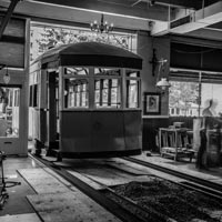black and white thumbnail of antique trolley being transported into the Old Spaghetti Factory on slide rails