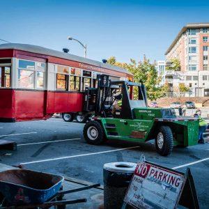 Omega Morgan caterpillar lifts antique trolley in parking lot