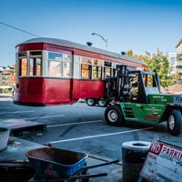 full color of Omega Morgan caterpillar lifting antique trolley in parking lot