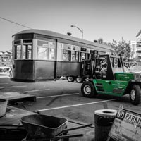 black and white and green thumbnail of Omega Morgan caterpillar lifting antique trolley in parking lot