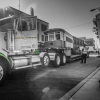 black and white thumbnail of Omega morgan truck parked with antique trolley on truck bed