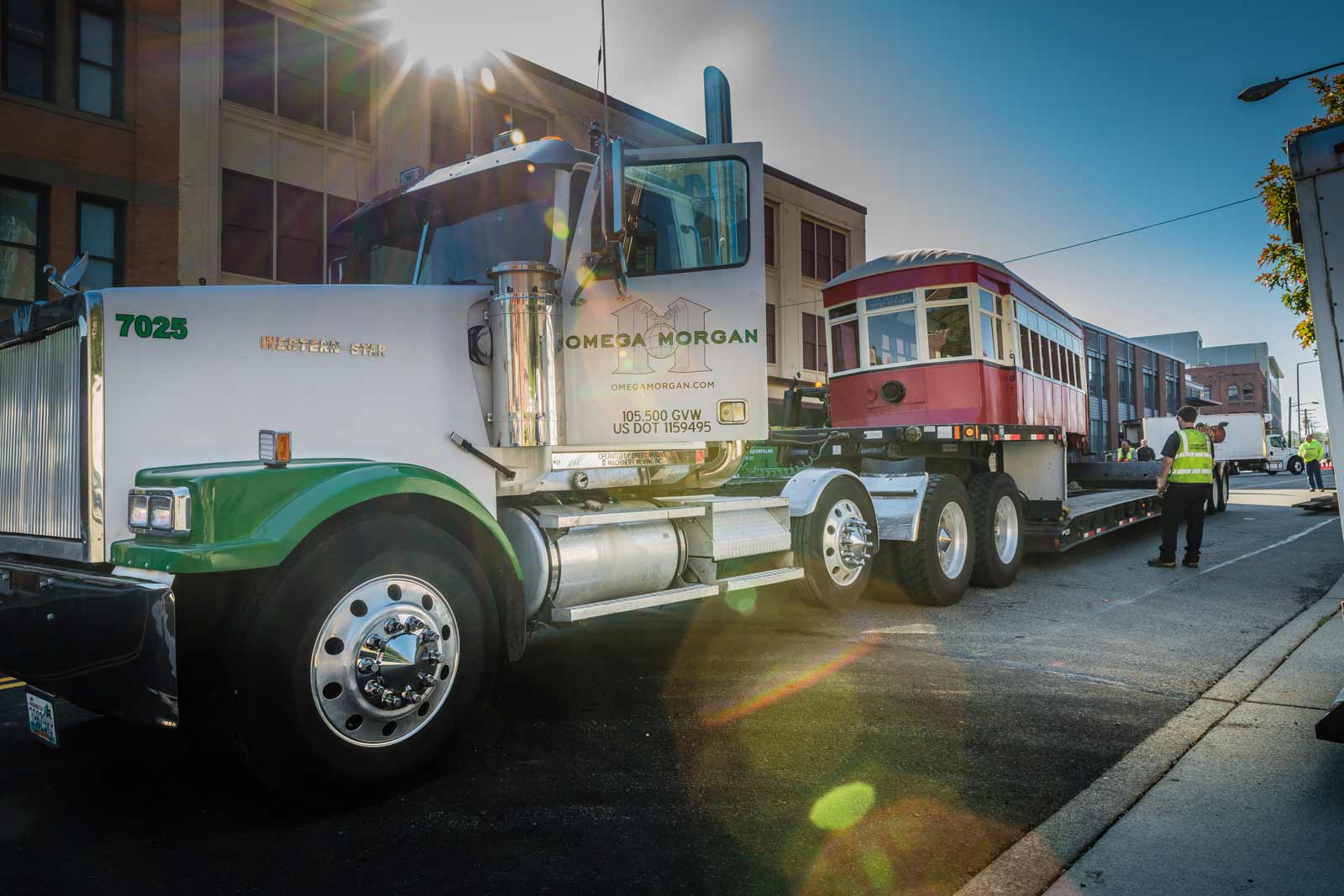 Omega morgan truck parked with antique trolley on truck bed