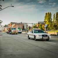full color thumbnail of police car escorting truck carrying old spaghetti antique trolley