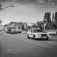 black and white and green thumbnail of police car escorting truck carrying old spaghetti antique trolley