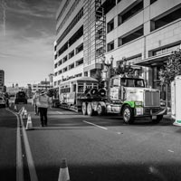 black and white and green thumbnail of Omega Morgan trailer and crews parked in front of downtown building preparing to move trolley car into Old Spaghetti Factory