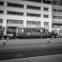 black and white and green thumbnail of trolley car on trailer in front of downtown building
