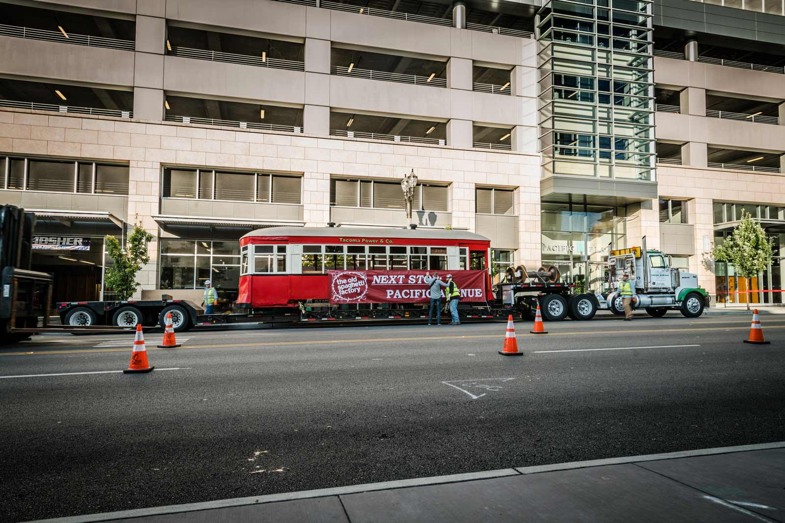 trolley car on trailer in front of downtown building