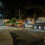 specialized transportation team trucks and trailers hauling tunnel boring machine through Seattle street at night