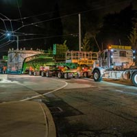 selected button thumbnail of specialized transportation team trucks and trailers hauling tunnel boring machine through Seattle street at night