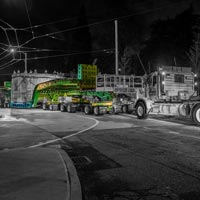 deselected button thumbnail of specialized transportation team trucks and trailers hauling tunnel boring machine through Seattle street at night