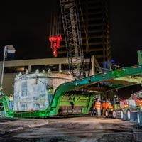 selected button thumbnail of tunnel boring machine on Omega Morgan transport with crane preparing to lift it