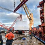 A turbine runner being lifted up towards the derrick crane barge for the journey down the inlet.