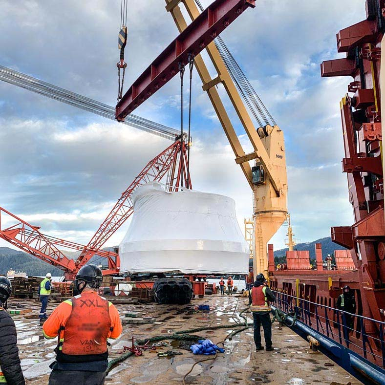 Omega Mogan team lifting a turbine runner towards a barge for water transport