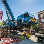 GMK 5220 crane working to pick and set six section vault on a street with an 18% grade in Seattle