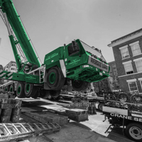 black and white and green thumbnail of GMK 5220 crane working to pick and set six section vault on a street with an 18% grade in Seattle